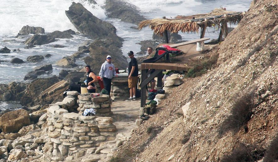 "FILE - In this Jan. 22, 2016, file photo people stand at a stone structure at Rocky Point in Lunada Bay in the tony, seaside city of Palos Verdes Estates, Calif. The days are numbered for the ""Stone Fort,"" created by a territorial group of surfers known as the Bay Boys, erected illegally decades ago as part of their sustained battle to keep rival wave-riders from some of the best breaks in Southern California. The city, under pressure from the California Coastal Commission and others, on Tuesday, July 12, 2016,ordered the structure torn down amid complaints that its only purpose is as a staging area from which the Bay Boys can gather to harass other surfers. (Charles Bennett/Long Beach Press-Telegram via AP, File)"