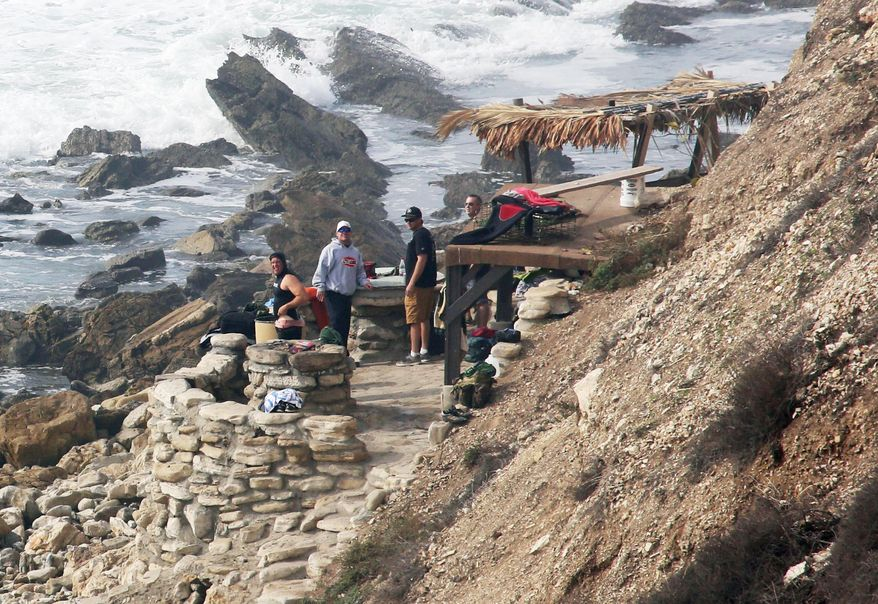 """FILE - In this Jan. 22, 2016, file photo people stand at a stone structure at Rocky Point in Lunada Bay in the tony, seaside city of Palos Verdes Estates, Calif. The days are numbered for the """"Stone Fort,"""" created by a territorial group of surfers known as the Bay Boys, erected illegally decades ago as part of their sustained battle to keep rival wave-riders from some of the best breaks in Southern California. The city, under pressure from the California Coastal Commission and others, on Tuesday, July 12, 2016,ordered the structure torn down amid complaints that its only purpose is as a staging area from which the Bay Boys can gather to harass other surfers. (Charles Bennett/Long Beach Press-Telegram via AP, File)"""