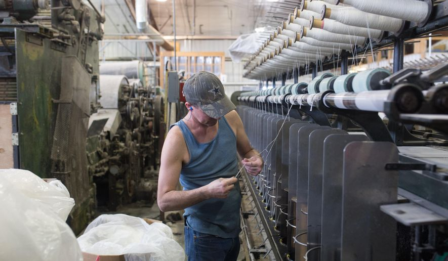 In this April 22, 2016 photo, Greg Warax, maintains machinery winding yarn onto spools at the Mountain Meadow Wool Mill in Buffalo, Wy. The family owned business is the largest full-service wool spinning mill in the West. (Jenna VonHofe/Casper Star-Tribune via AP)