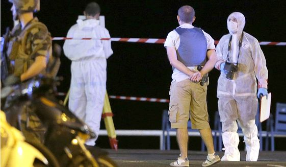 Forensic officers work at the scene of the truck attack that targeted Bastille Day revelers in Nice, France, on Friday. (Associated Press)