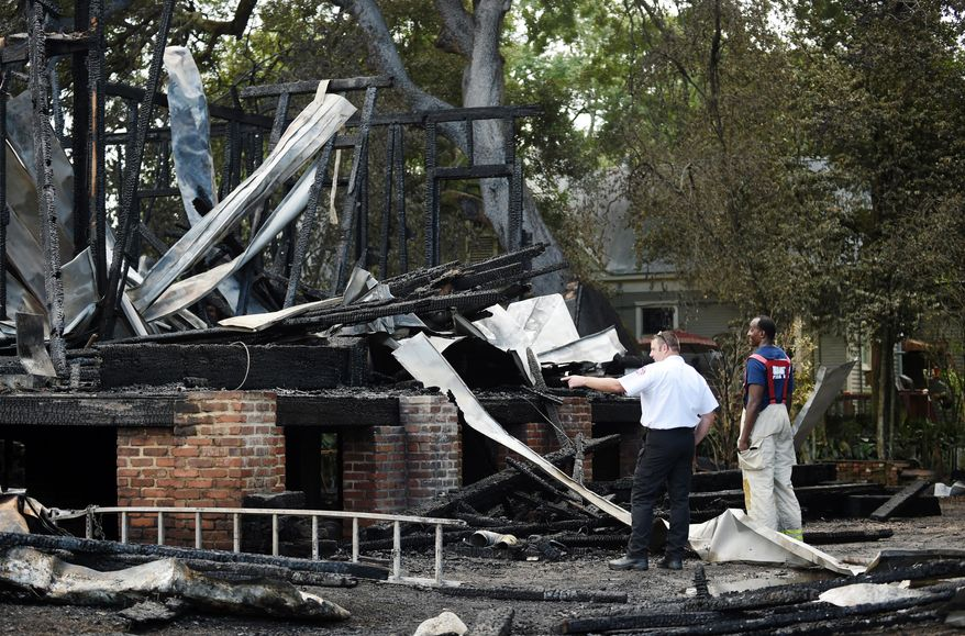 Opelousas Fire Chief Charles Mason, right, and Matt Rabalais, a training officer for St. Landry Fire Dist. 3, investigate the site of the old Governor's Mansion, in Opelousas, La., after the house was destroyed following a fire Thursday, July 14, 2016. Fire officials are still investigating the cause of the blaze. The house, which was under renovation, served as the Governor's Mansion for Gov. Thomas O. Moore during the Civil War in 1862 and 1863. (Leslie Westbrook/The Advocate via AP)
