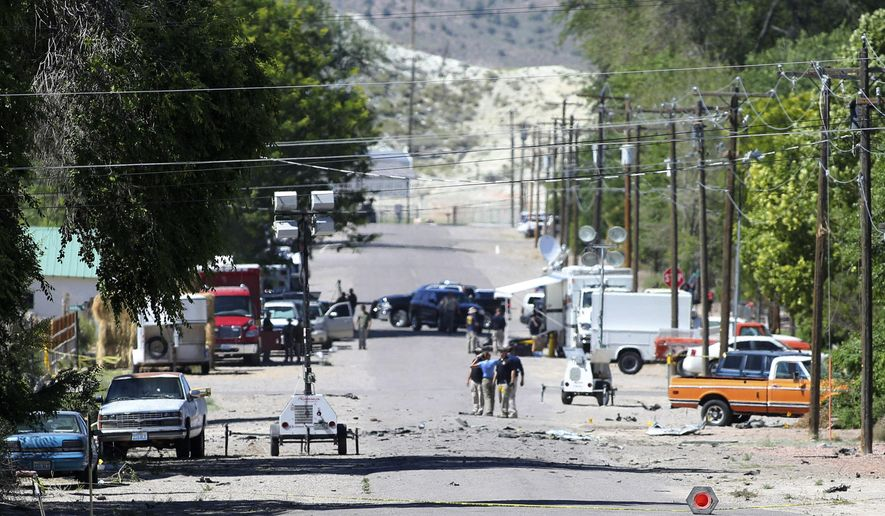 Police investigate shrapnel from a Wednesday night bombing that killed one person on 5th Street in Panaca, Nev., on Thursday, July 14, 2016. (Brett Le Blanc/Las Vegas Review-Journal via AP)