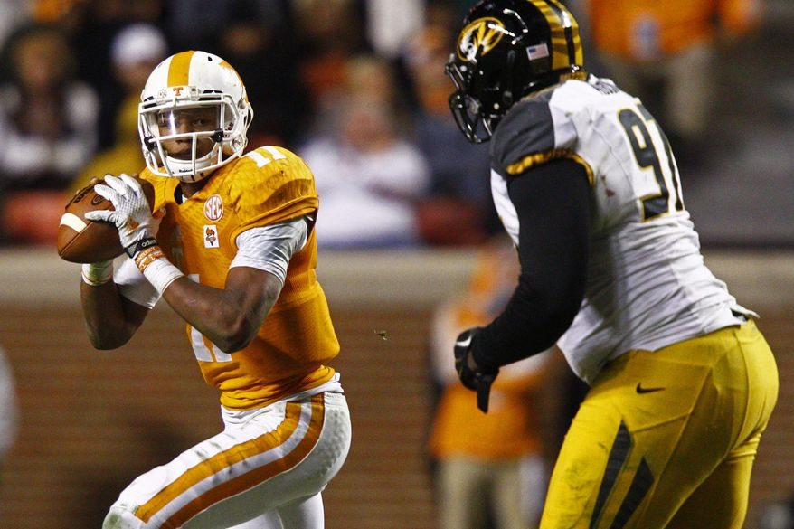 FILE - In this Nov. 22, 2014 file photo, Tennessee quarterback Joshua Dobbs (11) looks for a receiver as he's pressured by Missouri defensive lineman Josh Augusta (97) in the second half of an NCAA college football game in Knoxville, Tenn. No one player ever determines the fortunes of a team, although the quarterback is going to be important everywhere in the Southeastern Conference this season - except maybe Alabama. Six players, including Dobbs, will play a big role in determining how things shake out in the SEC. (AP Photo/Wade Payne, File)