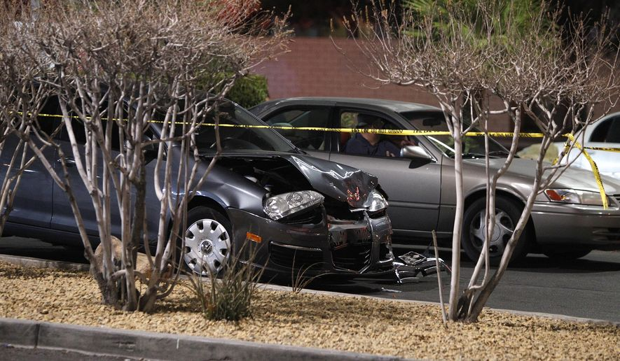 In this Jan. 21, 2014, file photo, a damaged car is seen at the scene of a fatal road rage incident near the corner of Tropicana Avenue and Rainbow Boulevard in Las Vegas. Authorities say a man shot a motorist to death in a vehicle with two children in the backseat in an apparent road-rage confrontation during rush-hour several miles west of the Las Vegas Strip. Nearly eight of every 10 U.S. drivers admit expressing anger, aggression or road rage at least once in the previous year, according to a new survey released Thursday, July 13, 2016, by the AAA Foundation for Traffic Safety. (John Locher/Las Vegas Review-Journal via AP, File)