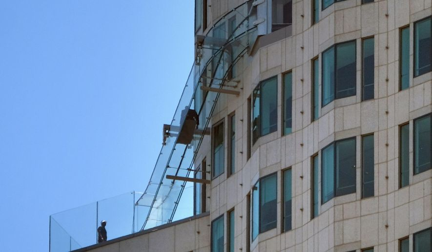 FILE - This Wednesday, June 22, 2016 file photo shows a man rides down a glass slide on the U.S. Bank Tower in downtown Los Angeles. A lawsuit claims a woman suffered a broken ankle on the recently opened glass-enclosed slide attached to the exterior of a downtown Los Angeles skyscraper. The lawsuit filed Wednesday, July 13, 2016, against building owner OUE Skyspace LLC and a concession company claims negligence. (AP Photo/Richard Vogel,File)