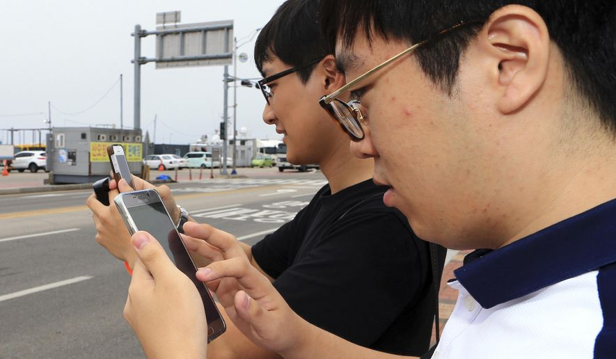 In this July 13, 2016 photo, two South Koreans play the Pokemon Go game with their mobile phones in Sokcho, South Korea. The seaside South Korean city of Sokcho is enjoying a surge of visitors who are wandering the streets at all hours as they look at their smartphones. It appears to be the only place in the country where Pokemon Go players can chase the mobile game's virtual monsters. (Lee Jong-hun/Yonhap via AP)