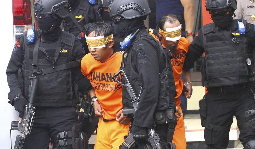 FILE - In this Feb. 21, 2016, file photo, Indonesian police officers escort suspected militants arrested in raids in Malang, East Java, Indonesia. Terrorism experts say the threat from the militants, spread across predominantly Muslim Indonesia, Malaysia and the southern Philippines, should not be underestimated and they could be transformed into a more dangerous force by training and leadership. (AP Photo/H.Y. Prabowo, File)