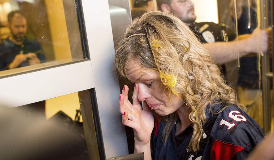 File - In this June 2, 2016 file photo a woman wipes egg off her face after being pursued by protesters while leaving Republican presidential candidate Donald Trump's campaign rally in San Jose, Calif. Fourteen California Donald Trump supporters filed a civil rights lawsuit Thursday, July 14, 2016, saying that San Jose's police failed to protect them from violent protesters after a campaign rally last month. The lawsuit is seeking class-action status on behalf of all Trump supporters who were attacked after the June 2 campaign rally in downtown San Jose.  (AP Photo/Noah Berger, File)