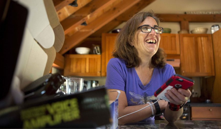 In this Friday, June 24, 2016, photo, Jessie Levine smiles as she listens to her recorded outgoing phone message on her iPhone in Springfield, N.H. Levine was diagnosed with Lou Gehrig's disease or ALS in 2015, and it has caused her speech to become slow and slurred. She is now exploring a new way to restore her voice via speech synthesis, or the artificial production of human speech. (AP Photo/Jim Cole)
