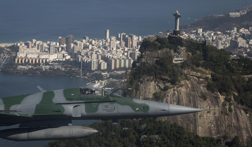 A F-5 fighter flies past the Christ the Redeemer statue while intercepting another aircraft, photographed through a window, during a Brazilian Air Force presentation for the press ahead of the Olympic games in Rio de Janeiro, Brazil, Thursday, July 14, 2016. (AP Photo/Felipe Dana)