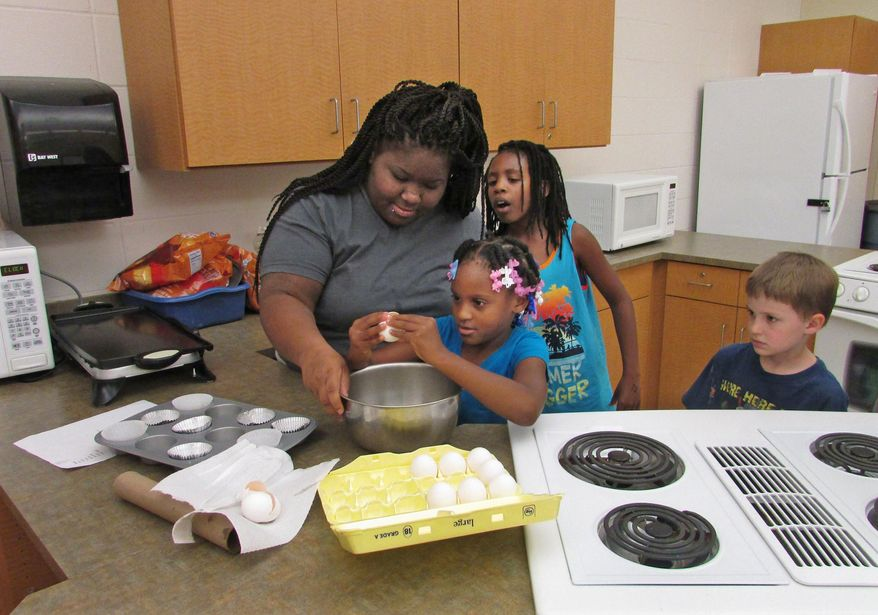 In this June 16, 2016 photo, counselor D'Aunniah Powell supervises and LaMara Cliff, 8, carefully cracks an egg at Camp Connections as Powell teaches kids how to make omelets in muffin tins in Decatur, Ill. Camp Connections' theme this summer is making healthy choices. (Valerie Wells/Herald & Review via AP)