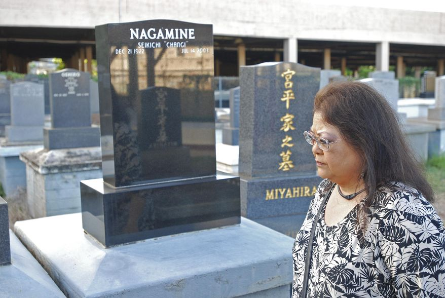 In this photo taken Wednesday, July 13, 2016, Lisa Wond visits a family grave site in Pearl City, Hawaii. Wond was devastated when urns containing her grandparents' and other family members' ashes were stolen from the site. Hawaii recently made it a felony to steal an urn. (AP Photo/By Cathy Bussewitz)