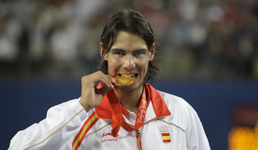FILE - In this Aug. 17, 2008, file photo, Rafael Nadal of Spain bites his gold medal after beating Fernando Gonzalez of Chile during their gold medal singles tennis match at the Beijing 2008 Olympics in Beijing. Nadal is on the final entry list for the Rio Olympics. The 14-time major champion hasn't played since pulling out of the French Open because of an injured left wrist and needed the International Tennis Federation's Olympic Committee to approve his appeal because he hasn't played Davis Cup. (AP Photo/Elise Amendola, File)