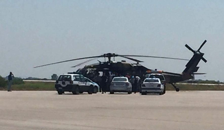 Greek policemen check a Turkish Blackhawk helicopter after landing at the airport of Alexandroupolis, northeastern Greece, on Saturday, July 16, 2016. Greece's defense ministry says a Blackhawk military helicopter carrying seven Turkish military personnel and one civilian has landed at the airport in the city of Alexandroupolis in northeastern Greece. The passengers have asked for asylum. They were arrested for illegal entry into Greece. (E-evros.gr via AP)