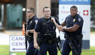 Police guard the emergency room entrance of Our Lady Of The Lake Medical Center, where wounded officers were brought, in Baton Rouge, La., on Sunday. (Associated Press)
