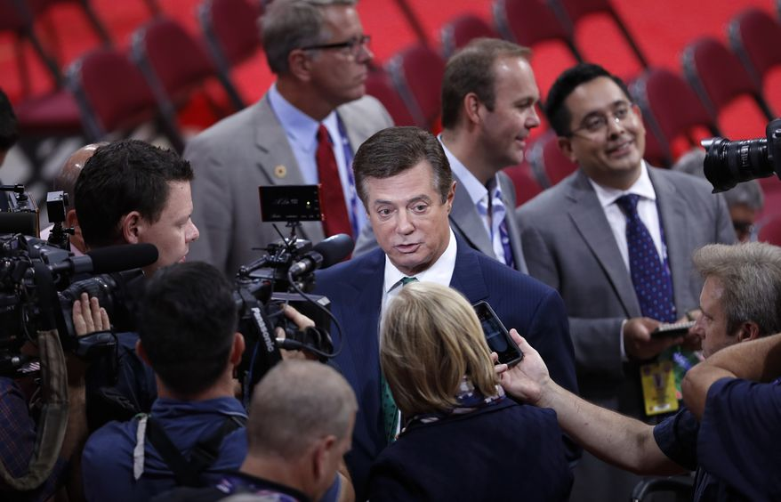 Trump Campaign Chairman Paul Manafort is surrounded by reporters on the floor of the Republican National Convention in Cleveland, Sunday, July 17, 2016. Donald Trump's presidential campaign has hired new staffers to manage the efforts of newly named vice presidential candidate Gov. Mike Pence of Indiana. (AP Photo/J. Scott Applewhite)