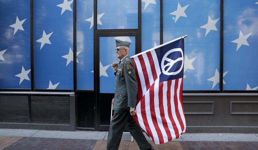 A protester carrying a peace flag walks in downtown Cleveland, Sunday, July 17, 2016, in preparation for the Republican National Convention that starts Monday. (AP Photo/Patrick Semansky)