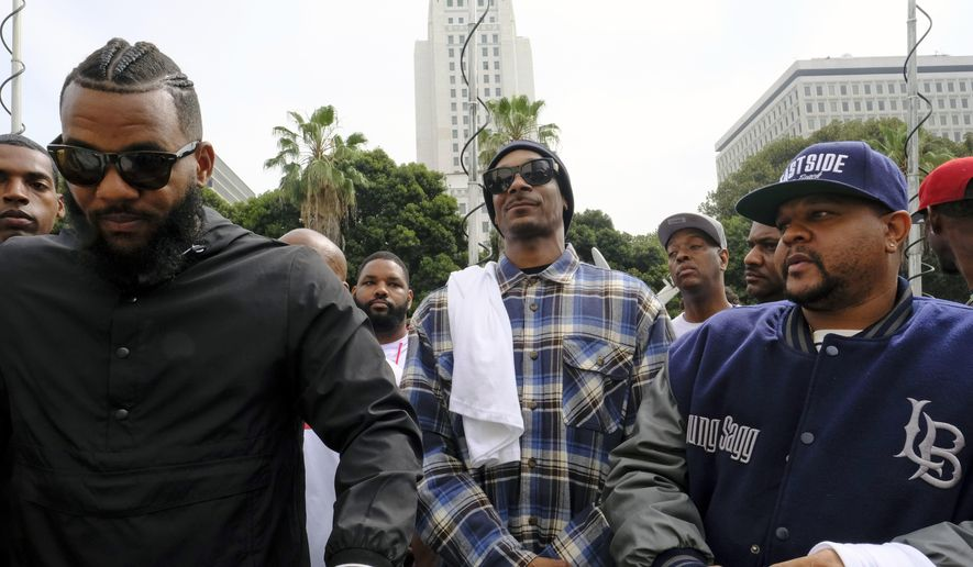 In this Friday, July 8, 2016, file photo, rappers The Game, left, and Snoop Dogg, center, appear at a peaceful unification march outside of the graduation ceremony for the latest class of Los Angeles Police Department recruits, in Los Angeles. (AP Photo/Richard Vogel, File)