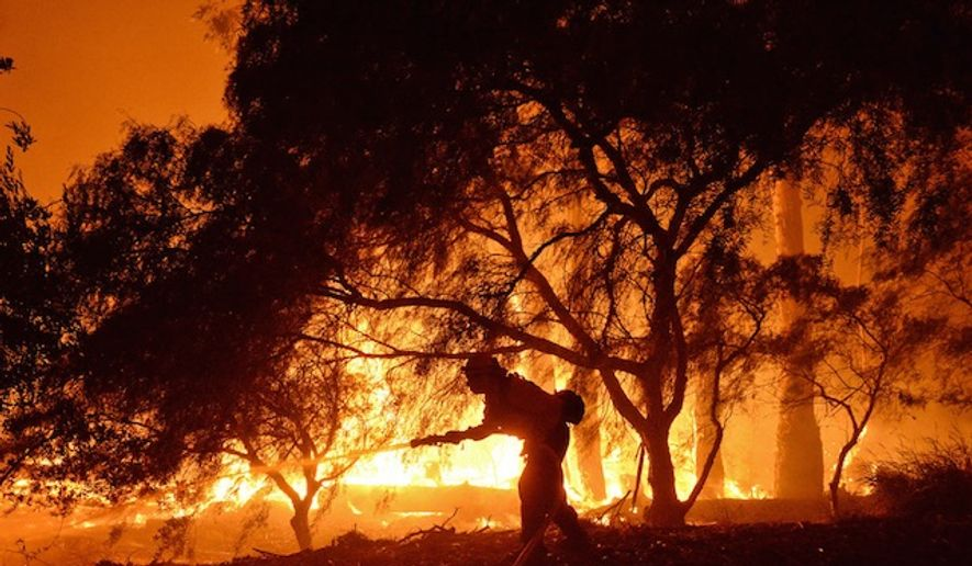 A firefighter battles flames near the Las Flores Canyon area west of Goleta, Calif., June 16, 2016. (Mike Eliason/Santa Barbara County Fire Department via AP) ** FILE **