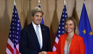 European Union High Representative Federica Mogherini, right, shakes hands with U.S. Secretary of State John Kerry at the EU Council building in Brussels, Belgium, Monday, July 18, 2016. (AP Photo/Darko Vojinovic)