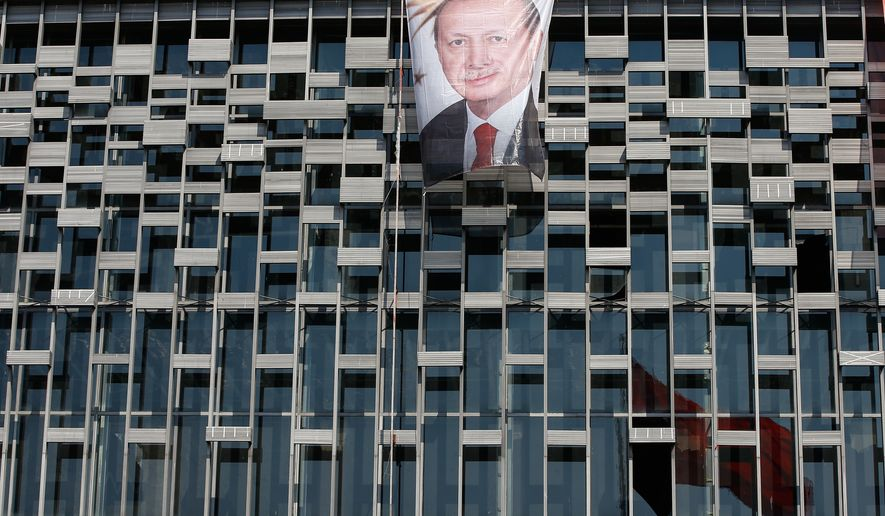 A poster of Turkey's President Recep Tayyip Erdogan hangs on a building near Taksim Monument in Istanbul, Monday, July 18, 2016. (AP Photo/Emrah Gurel)