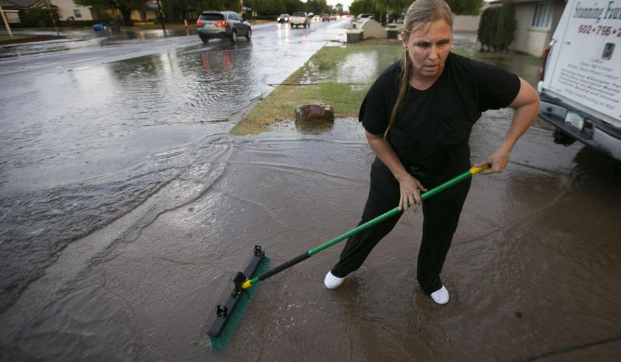 Silvia Graham sweeps water out of her driveway in front of her home, as 40th Street floods south of Thomas Road in Phoenix, following heavy rains on Monday evening, July 18, 2016. Her home flooded a little bit from the backed up water. (David Wallace/The Arizona Republic via AP)