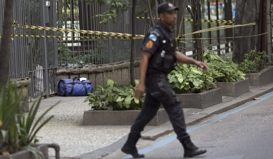 A police officer walks near a backpack deemed suspicious that was left at the door of an apartment building, in the Leblon neighborhood of Rio de Janeiro, Brazil, Monday, July 18, 2016. With the Olympics set to start on Aug. 5, the games and the city have been overshadowed by security threats, violence, the Zika virus and a national political corruption scandal. (AP Photo/Silvia Izquierdo)
