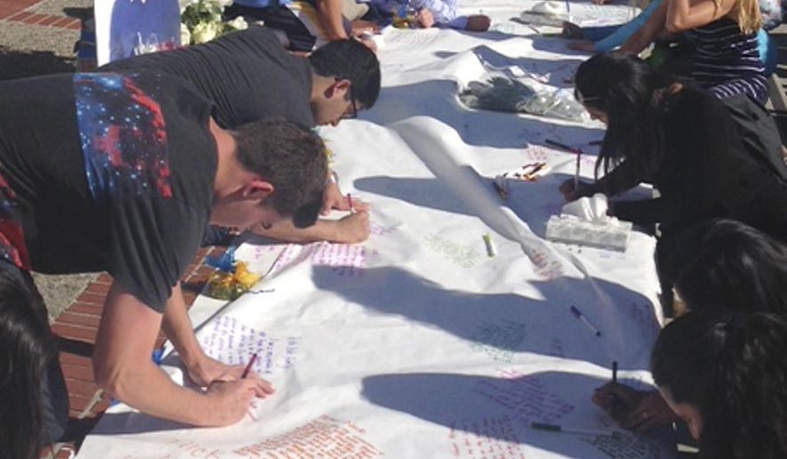Students leave condolences on a banner for Nicolas Leslie, who was killed in France last week, during a vigil at the University of California, Berkeley Monday, July 18, 2016 in Berkeley, Calif. Leslie, 20, a Berkeley student who was killed in last week's Bastille Day truck attack in France was remembered Monday as an energetic and engaged member of the campus community. Leslie was an aspiring entrepreneur and environmentalist who participated in fraternity life and a student-run consulting group that provides marketing, research and social responsibility advice to businesses, student body President William Morrow said. (AP Photo/Lisa Leff)