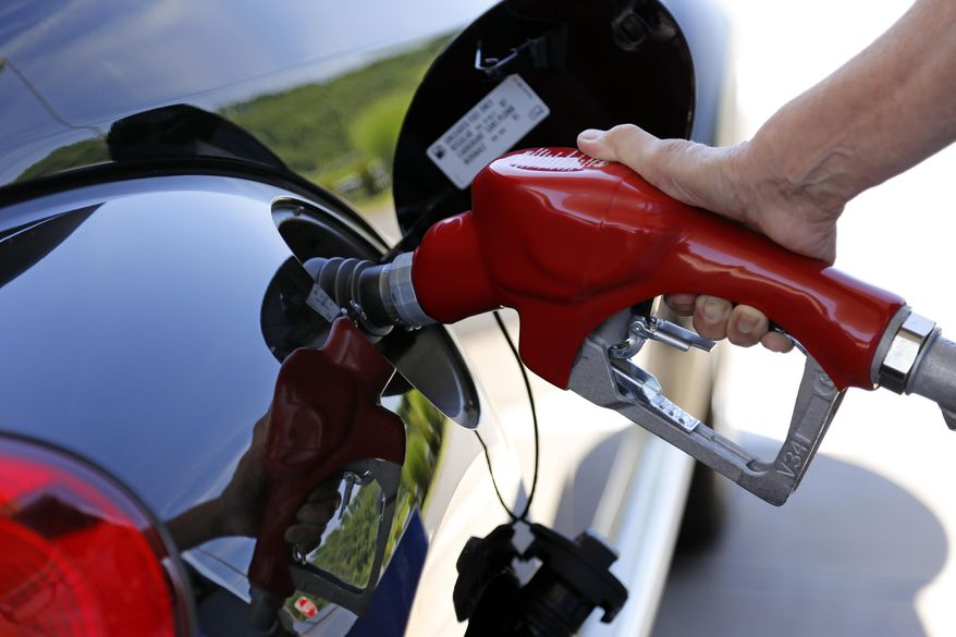 In this Thursday, July 16, 2015, file photo, a customer re-fuels her car at a Costco in Robinson Township, Pa. The U.S. government says the fuel economy of the nation's fleet of cars and trucks likely won't meet its targets in 2025 because low gas prices have changed the types of vehicles people are buying. (AP Photo/Gene J. Puskar)
