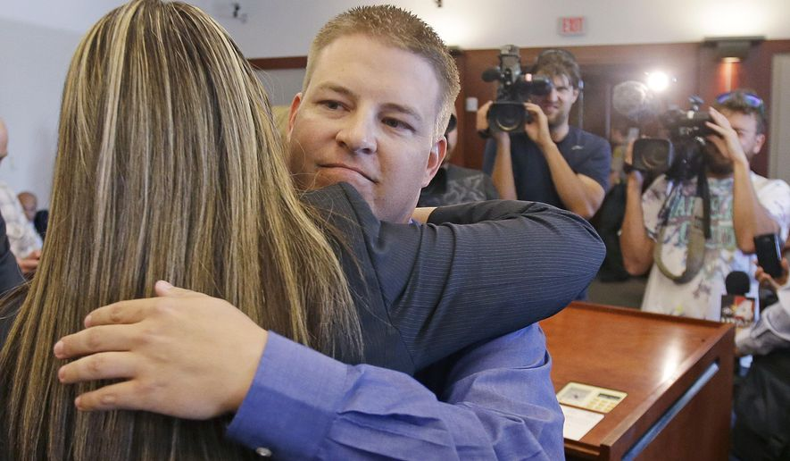 FILE - In this Thursday, Oct. 9, 2014, file photo, former West Valley City police officer Shaun Cowley gets a hug from his defense attorney Lindsay Jarvis after being dismissed of a manslaughter charge in Salt Lake City. A judge is tossing out several key parts of a civil rights lawsuit brought against West Valley City by Cowley who claims his reputation was ruined following his firing after he fatally shot a woman during a drug investigation. (AP Photo/Rick Bowmer, File)
