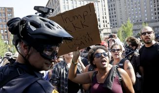 Republican presidential candidate Donald Trump protesters yell as police look on at Public Square Tuesday, July 19, 2016, in Cleveland, during the second day of the Republican convention. (AP Photo/Patrick Semansky)