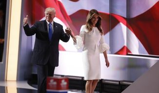 Republican presidential candidate Donald Trump walks wife Melania on stage during the opening day of the Republican National Convention in Cleveland, Monday, July 18, 2016. (AP Photo/Paul Sancya)
