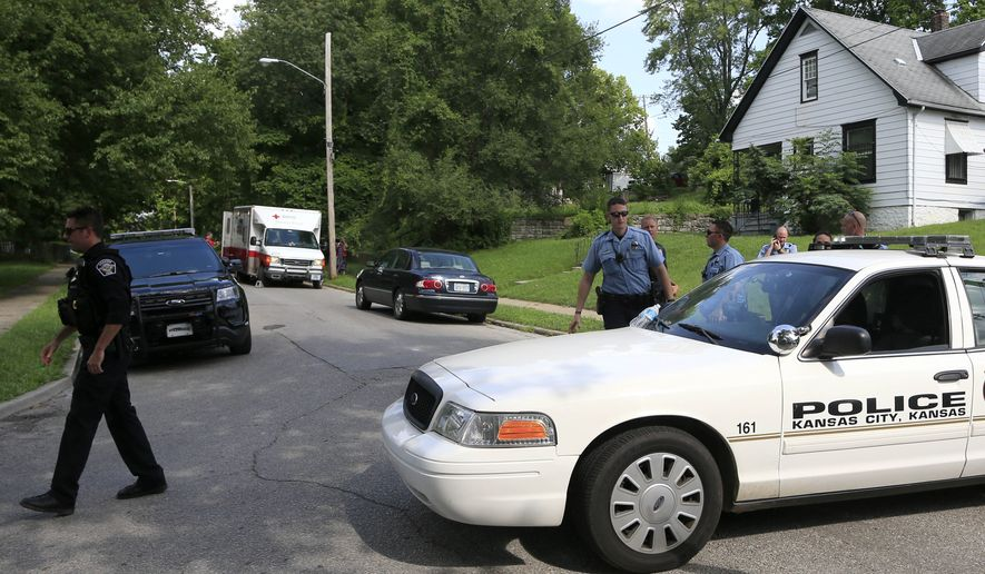 Kansas City, Kan., and Shawnee police officers work part of the shooting scene of a police officer in Kansas City, Kan., Tuesday, July 19, 2016. A suspect in a drive-by shooting fatally shot Capt. Robert Melton, a 17-year veteran of the Kansas City, Kan., Police Department, on Tuesday as the officer was sitting in his patrol car, police said. (AP Photo/Orlin Wagner)
