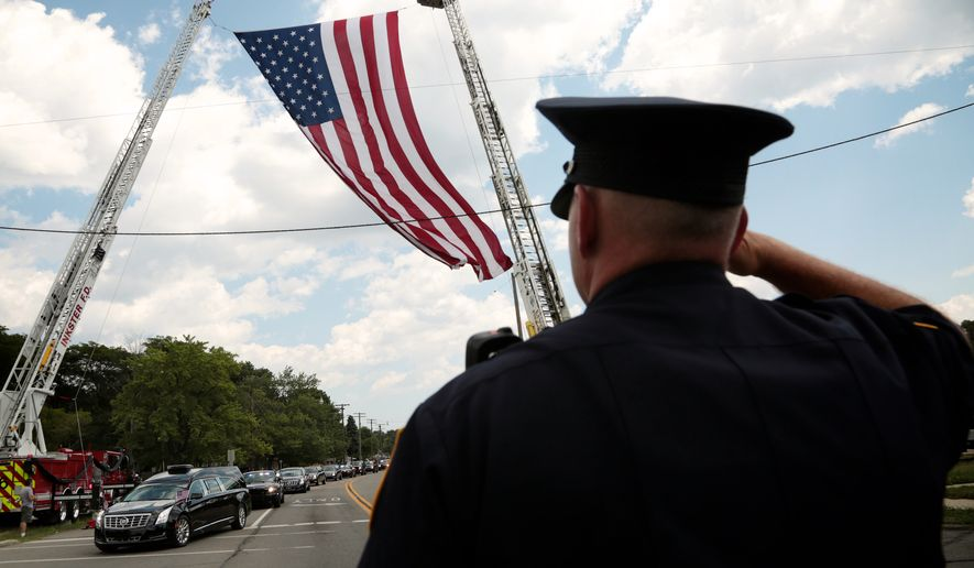 Livonia Police officer Dave Scott salutes as the funeral procession for  Dallas Police officer Michael Krol leaves St. Robert Bellarmine Catholic Church, Tuesday, July 19, 2016 in Redford Township, Mich. (Salwan Georges/Detroit Free Press via AP)