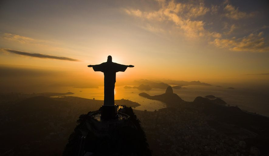 The sun rises behind the Christ the Redeemer statue, above the Guanabara bay in Rio de Janeiro, Brazil, Tuesday, July 19, 2016. (AP Photo/Felipe Dana)