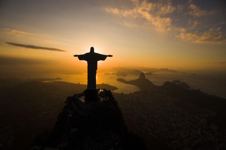The sun rises behind the Christ the Redeemer statue, above the Guanabara bay in Rio de Janeiro, Brazil, Tuesday, July 19, 2016. (AP Photo/Felipe Dana)