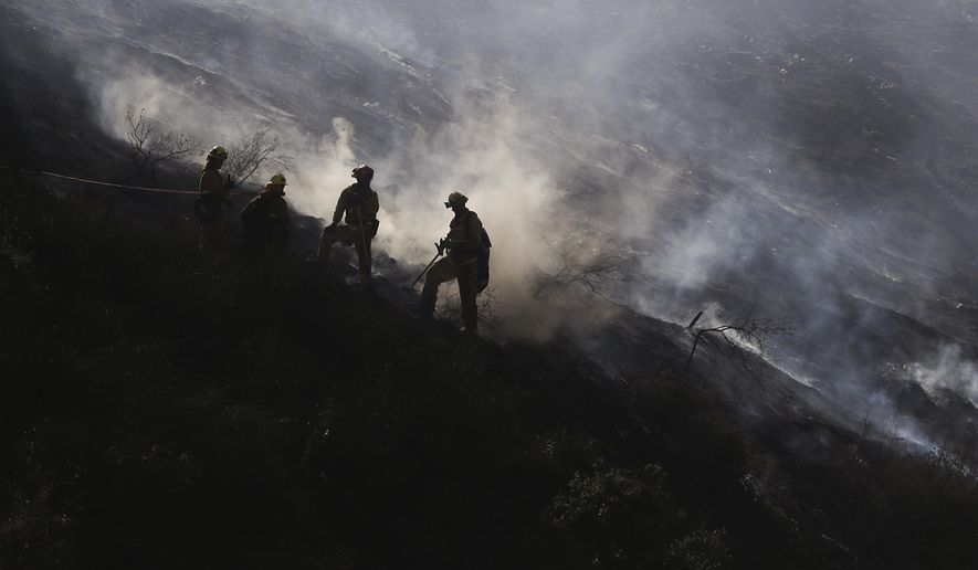 Firefighters stand on a scorched hillside as a wildfire burns in the Hollywood Hills section of Los Angeles, Tuesday, July 19, 2016. The blaze broke out shortly after 3 p.m. Tuesday near the Hollywood Reservoir. Fire crews and the dramatic sight of flames and smoke combined to slow traffic on the nearby U.S. 101 Freeway as rush hour was beginning. (AP Photo/Jae C. Hong)