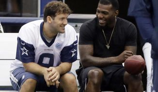 FILE - In this June 18, 2015, file photo, Dallas Cowboys wide receiver Dez Bryant, right, sits on the bench with quarterback Tony Romo (9) during NFL football minicamp at the team's stadium in Arlington, Texas. Both are anxious to get on the field together after injuries kept them apart most of last season, when Dallas slid from first to worst in the NFC East. (AP Photo/LM Otero, File)