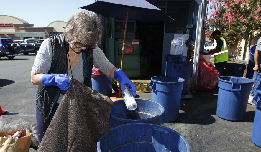 In this photo taken Tuesday, July 5, 2016 Claudette Cole places a plastic bottle into a plastic container at a recycling center in Sacramento, Calif. More than 450 recycling centers statewide have closed in the last year, stripping millions of consumers of easy access to recycling services. (AP Photo/Rich Pedroncelli)