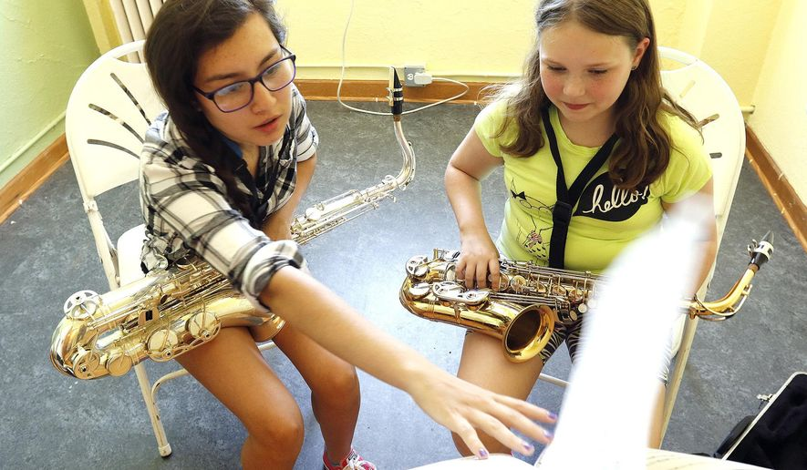 In this June 15, 2016 photo, Crystal Lake South high school junior Vanessa Rodriguez, left, and sixth grader Kassi Hovi look over notes during a mentoring session at the Lakeside Legacy Foundation in Crystal Lake, Ill. Music Mentors started four years ago, matching up junior high musicians with high school mentors to keep them practicing their instruments over the summer. Hovi has been playing the saxophone for just over a year. (H. Rick Bamman/Northwest Herald via AP)