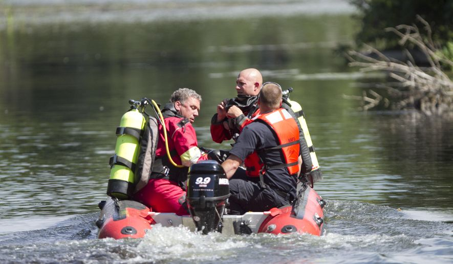 In this Monday, July 18, 2016 photo, the Livingston County Sheriff's Dive Team heads out to search for an 18-year-old man later identified as Andrew Massey, whose body was then recovered from drowning, on Handy Lake in Hartland Township, Mich. (Gillis Benedict /Livingston County Daily Press & Argus via AP)