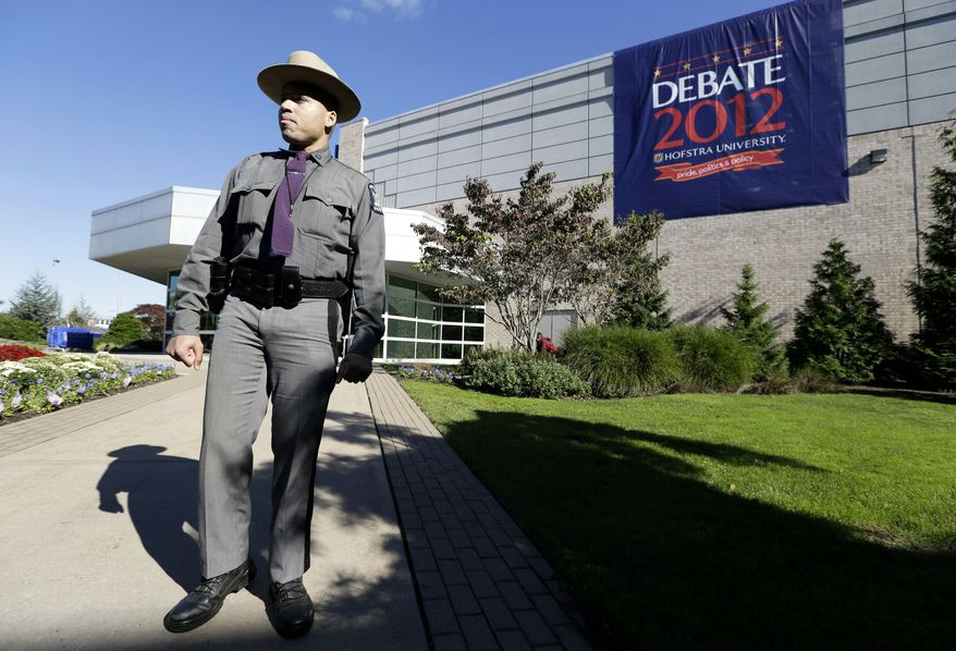 FILE – In this Oct. 16, 2012, file photo, New York state trooper Gary DePass stands outside the site of a debate later that day between President Barack Obama and the Republican presidential nominee, former Massachusetts Gov. Mitt Romney, at Hofstra University's David S. Mack Sports Complex in Hempstead, N.Y. The Commission on Presidential Debates announced Tuesday, July 19, 2016, that Hofstra University will host the 2016 general election's first presidential debate on Monday, Sept. 26, 2016, after Wright State University in Ohio withdrew due to security concerns and costs. (AP Photo/Charlie Neibergall, File)