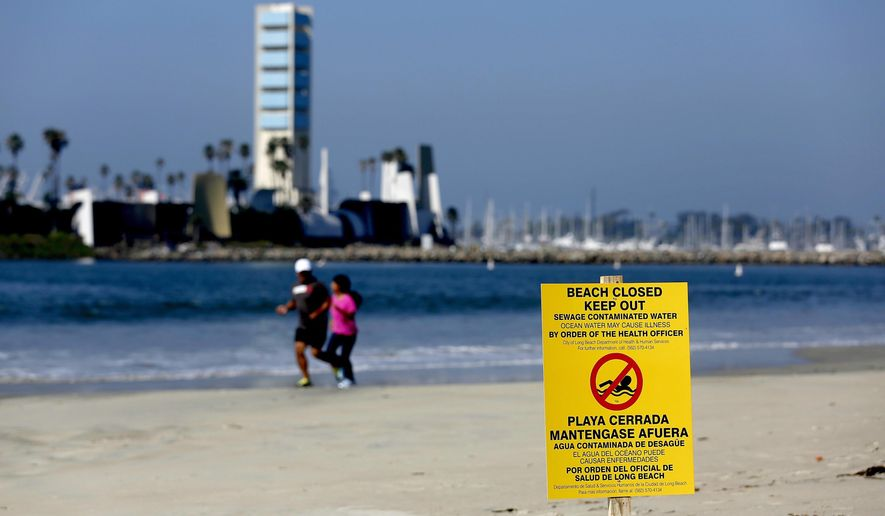 A sign is posted on a beach warning of the dangers of sewage contaminated water Tuesday, July 19, 2016, in Long Beach, Calif. Beaches in Long Beach have been shut down after a sewage spill that began near downtown Los Angeles the day before, flowed down the LA River to the ocean. Long Beach officials estimate that more than 100,000 gallons of sewage reached the city, and its ocean waters will be closed until testing shows it's safe. (Gary Coronado/Los Angeles Times via AP)