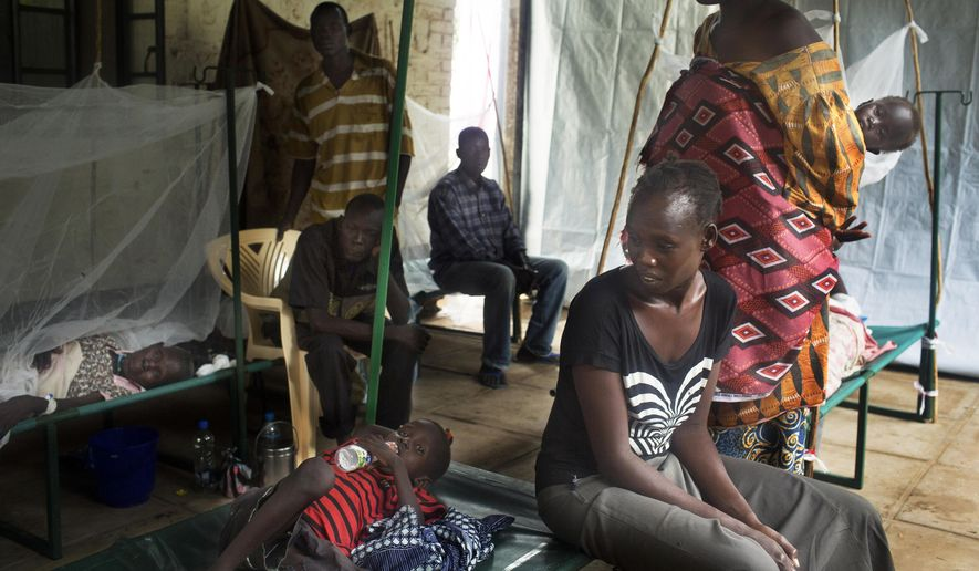 FILE--- In this  Saturday May 24, 2014 file photo a South-Sudanese family waits in the cholera isolation ward of Juba Teaching Hospital in the capital Juba, South Sudan. UNICEF says 11 people have died in a suspected cholera outbreak in South Sudan. The organization said Tuesday there are 72 suspected cases so far, including 36 in the capital, Juba. Others are in Bor and Terekeka counties.(AP Photo/Matthew Abbott/file)