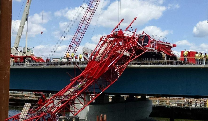 A giant crane sits on the Tappan Zee Bridge north of New York City after toppling around noon on Tuesday, July 19, 2016, during construction of a new bridge, across the Hudson River between Westchester and Rockland counties. The base and treads of the huge, moveable crane sat on the unfinished new bridge while part of the toppled crane lay across the lanes of the old bridge and another section lay across a construction platform in the water between the two spans. (David Leibstein via AP)