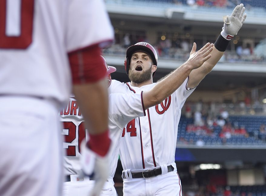 Washington Nationals' Bryce Harper, back, celebrates his two-run home run with Daniel Murphy, center, during the first inning of a baseball game against the Los Angeles Dodgers, Wednesday, July 20, 2016, in Washington. (AP Photo/Nick Wass)
