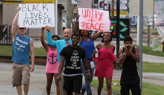 A group of protesters march along U.S. Route 412 in Lexington, Tenn., Tuesday, July 19, 2016. (C.B. Schmelter/The Jackson Sun via AP) ** FILE **