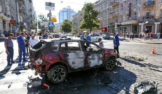 Forensic experts examine the wreckage of a burned car in Kiev, Ukraine, Wednesday, July 20, 2016. Pavel Sheremet, 44-year old Belarusian-born prominent journalist was killed in a car bombing in Ukraine's capital Kiev. (AP Photo/Sergei Chuzavkov)