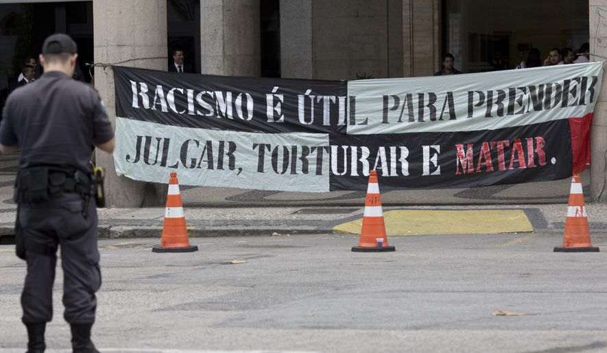 "A police officer stands in front a banner that reads in Portuguese: ""Racism is useful to arrest, judge, torture and kill"" during a demonstration against racism and police violence, in Rio de Janeiro, Brazil, Wednesday, July 20, 2016. A delegation of activists from the Black Lives Matter movement is in Rio de Janeiro to highlight racism and police violence in the Olympic city ahead of the summer games. The six United States activists are meeting over four days with families of local victims of police violence, as well as community leaders and anti-racism activists. (AP Photo/Silvia Izquierdo)"