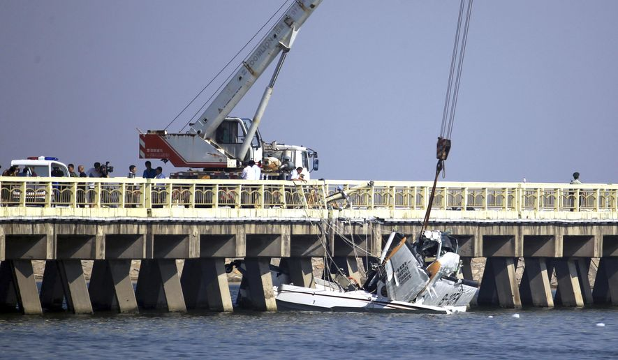 A damaged seaplane is lifted from a highway bridge in Shanghai Wednesday, July 20, 2016. The seaplane making its inaugural flight crashed into the bridge on Wednesday, killing several people on board, state media reported. (Chinatopix via AP)